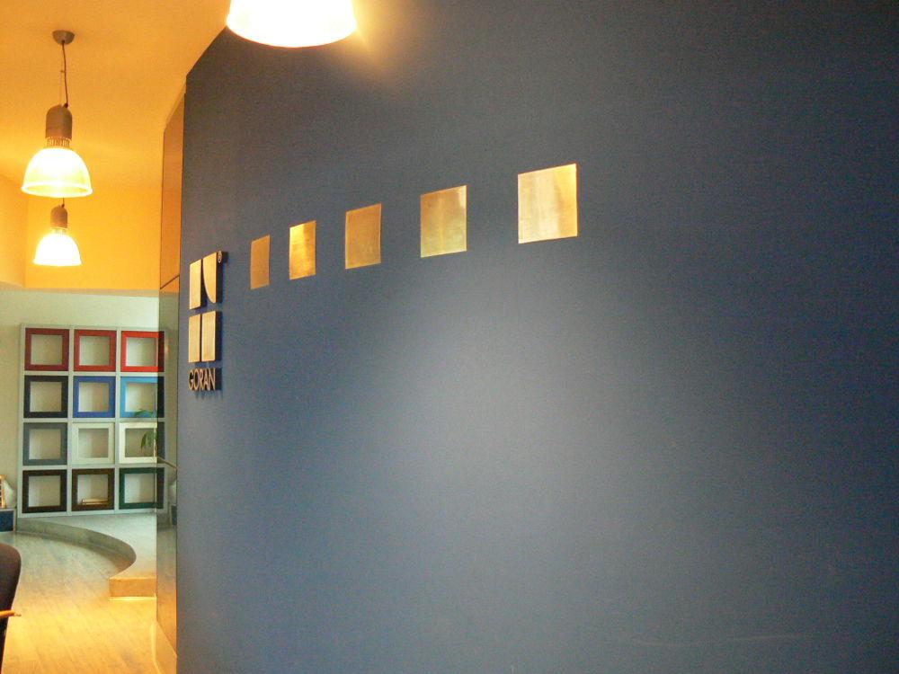 Szara ściana z logo w salonie stolarki budowlanej Goran